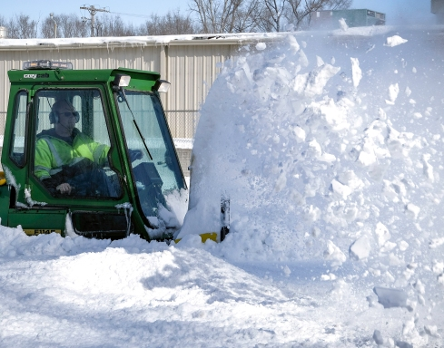 CJ Heaton cleans removes snow from the Rich Warrick Memorial Park sidewalks along 19th street.