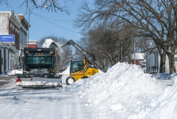 Arlington city crews remove snow piled in the middle of Arlington streets Sunday afternoon.