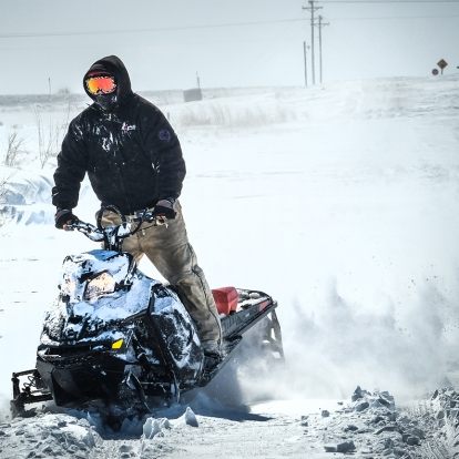 Joel Nelson rides his snow mobile through snow drifts on County road 17 Sunday afternoon. Many county roads were impassable Sunday afternoon due to blowing and drifting snow. Snow cleanup in W. County